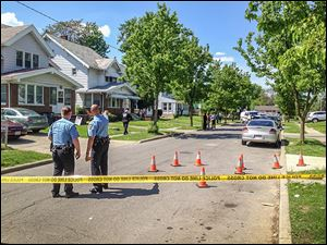 Toledo police officers survey the scene of  shootings in the 2100 block of Joffre Avenue, east of Upton Avenue and Bancroft Street.