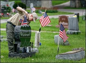 Cory Johnson, 14, of Boy Scout Troop 8 places flags at Union Cemetery in Wauseon  for Memorial Day. In cemeteries across the country today, the Stars and Stripes will decorate veterans' graves.