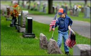Cub Scout Dominic Barone, 6, places flags at Union Cemetery Sunday in Wauseon.  The flag place­ment gives the scouts a chance to show their re­spect for those who bravely fought.