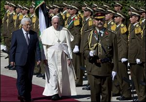Palestinian President Mahmoud Abbas, left, and Pope Francis inspect an honor guard as Francis arrives at the Palestinian Authority headquarters.