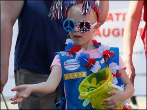Daisy Troop 10428 member Ellie Tuck, 6, of Toledo, passes out candy.