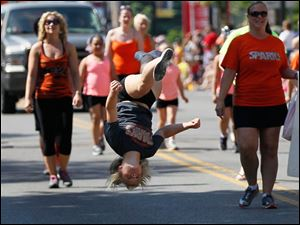 McKinly Gessner, 13, of Monroe, Michigan, does a flip as she and others in Sparks travel the parade route.