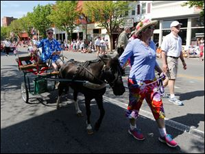 Stephanie White leads a donkey-pulling cart in the parade. Riding in the cart is Tim Broue.