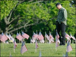 Tony Geer, of Sylvania, who served in the U.S. Army in the 1980s, looking at the graves in the veterans' section at Toledo Memorial Park.