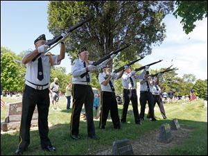 Bob Peeler, from left, Art Sobczak, Jack Shaffer, Bill King, Frank Brahier, and Eugene Mishka, members of American Legion Post 28 in Perrysburg, fire a rifle salute.