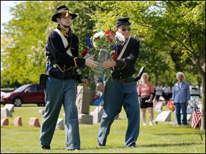 Drew Tompkins of Morenci, Michigan, left, and Robert May of Perrysburg, place a wreath.  The men are Civil War re-enactors.