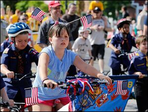 Grace Herron 9, of Perrysburg, is adorned with flags as she rides her bike.