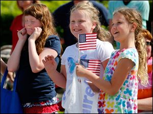 Julianne Schramm, 9, left, tries to block the parade sounds as Marissa Engel, 9, center, and Ashley Miller, 9.