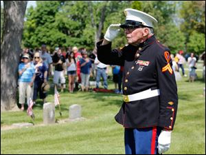 Marine Cpl. Bob Romaker, 87, salutes during the playing of the National Anthem. Corporal Romaker, 88, served at Iwo Jima during World War II.