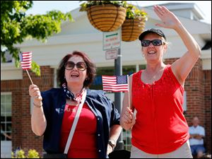 Melanie Teachout of Sylvania, left, and her sister, April Rector of Perrysburg, wave to participants.