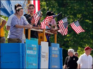 Richi St. Jean, 14, from left, David Fox, 13, (behind Richi) and Matt Fox, 17, wave flags as they ride on The Rotary Club of Perrysburg float.