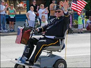 U.S. Army veteran John Parrish of Perrysburg, waves to spectators.  Parrish, who served in Korea, is a member of American Legion Post 28 and commander of VFW Post 6170.