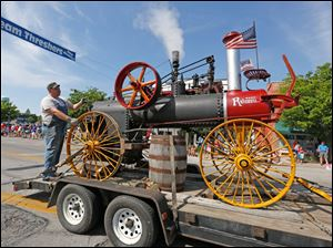 Zach Johnson of Perrysburg rides with a 1904 Russell steam engine. He is with the Five Point Steam Threshers.
