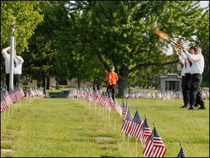 The color guard of American Legion Post #468 firing a 21-gun salute during the ceremony at Toledo Memorial Park.