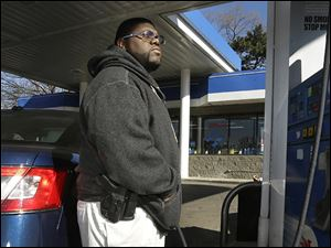 Greg Champion wears a gun while pumping gas in Detroit. To avoid becoming a carjacking victim, Mr. Champion wears a handgun on his hip whenever he is pumping gas. Through May 19, Detroit has recorded 191 carjackings in 2014.