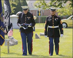 Retired Marine Cpl. Bob Romaker, left, and retired Gunnery Sgt. Juan Artiaga, both of Perrysburg, prepare to raise the flag at Fort Meigs Union Cemetery in Perrysburg during Monday's Memorial Day remembrance service.