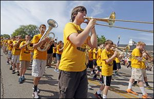 Aaron Polaff, 13, center, plays his trombone with the Perrysburg Junior High School band as the march in the parade.