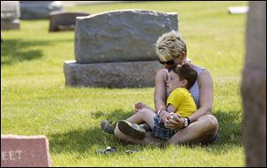 Patricia Gaffney, with her son, Alexander, 4, of Perrysburg bows her head in prayer at the Fort Meigs Union Cemetery service.