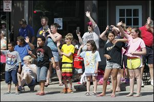 Children along the parade route in Sylvania wave as the marchers pass.     Hundreds of people crowd both sides of Main Street from the bridge over Ten Mile Creek to Erie Street for the parade. It was followed by a service at Veterans Memorial Field. Before the parade, the city hosted a ceremony at Toledo Memorial Park.