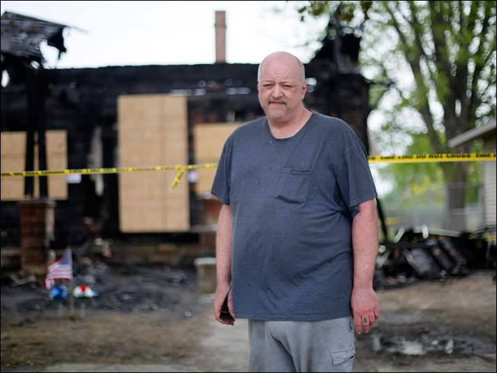 Neighbor Gary Zimmerman witnessed the fire at 614 Poplar St., in Fostoria, behind him,  where 2 people, including Danny Marker,  died in a fire on Monday.