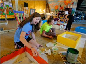 Abby Guenin, 14, left, and Maya Harmon, 12, paint butterfly boxes.