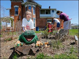 Alyssa Birkhimer, 5, climbs on a tree stump frog as Madison Harmon, 12,  and Arianna Willis, 12 , right, weed a garden in a field near the Sofia Quintero Center.