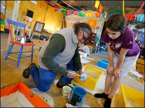 Joe Balderas helps Arianna Willis, 12, as they paint butterfly boxes.