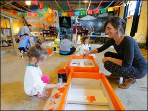 Tonia Birkhimer and her twin five year old daughters Alyssa, left, and Sophia, paint butterfly boxes.