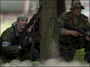 A pro-Russian gunman takes cover behind a tree during shooting near the airport, outside Donetsk, Ukraine, today.