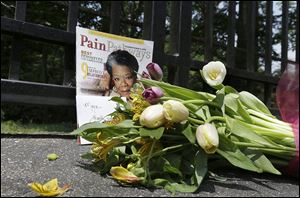 A bouquet and a magazine showing Maya Angelou on the cover are placed outside a gate at her home in Winston-Salem, N.C. She died Wednesday at age 86.