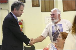 U.S. Sen. Sherrod Brown, left, greets Vietnam veteran Don Miller of Point Place before a news conference.