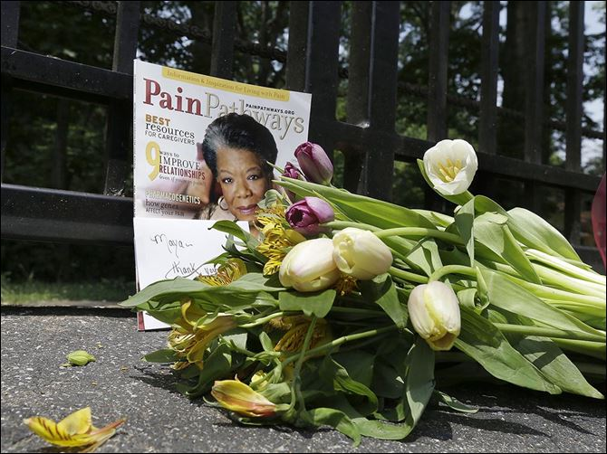 29n5flowers-1 A bouquet and a magazine showing Maya Angelou on the cover are placed outside a gate at her home in Winston-Salem, N.C. She died Wednesday at age 86.