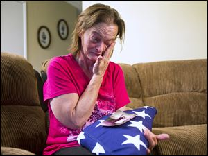 Vicky Olson wipes away a tear May 9 while talking about her husband, Michael Olson, a Marine veteran who died at home in their garage in March at age 45.  Vicky holds their wedding photograph , as well as a United States flag given to her at a memorial service for Michael.