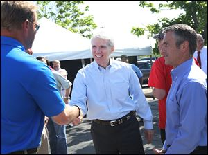 Sen. Rob Portman (R., Ohio), center, greets Chris Ostrander, left, Cooper Tire & Rubber Co.'s president of North American Tire Operations,  and Tom Lause, vice president of finance,  after addressing a crowd of employees Thursday at Cooper Tire & Rubber Co. in Findlay.