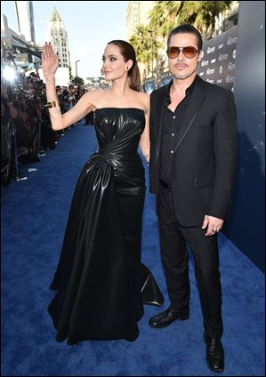 "Angelina Jolie, left, and Brad Pitt arrive at the world premiere of ""Maleficent."""