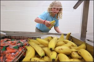 Laura Martin, 10, selects a banana during lunch at  Reynolds Elementary in South Toledo. Each lunch includes two fruits, one protein, one vegetable, and milk.  The school adopted the healthier menu in the past year.