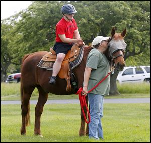 Ty Carroll, 14, of Rossford takes a ride on a horse called Big Red, who is guided by volunteer Joan Miller.