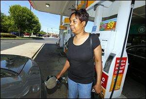 Danyale Brown fills a vehicle at the Shell station at Secor Road and Monroe Street on Friday.
