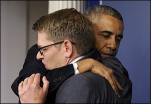 President Barack Obama gives White House press secretary Jay Carney a hug after announcing that Carney will step down later next month, during a surprise visit to the Brady Press Br