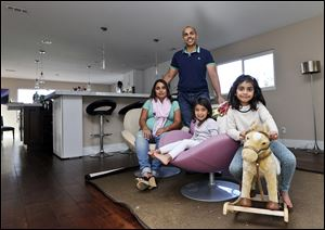 Imran and Aniqa Jaswal and children Arissa, right, and Jayda, pose in their house about 10 minutes from the beach in La Jolla, Calif., a state