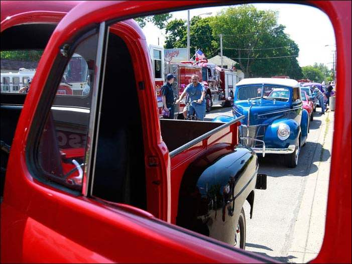 Antique cars, including this red 1948 Ford F1, line up for the Point Place Days parade down Summit St. in Toledo.