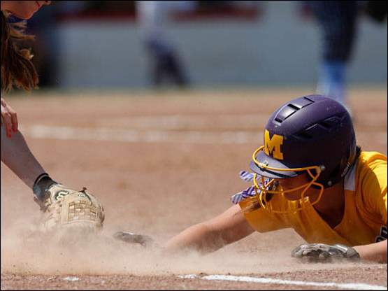 Maumee's Samantha Fowler dives safely back to first base.
