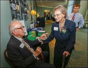 Dr. Peter White, left, professor emeritus, chats with Annabelle Isaacs, the first employee at the Medical College of Ohio, during the 50th anniversary celebration of its founding. At right is medical student Jonathan Demeter of Springfield, Ohio.