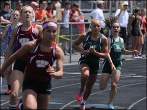 Oak Harbor's Cydney St. Clair is handed the baton from Karis DeWalt in the girls 4x400 relay.
