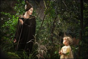 Angelina Jolie as Maleficent, left, in a scene with her daughter Vivienne Jolie-Pitt, portraying Young Aurora.