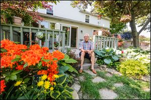 Kevin Kwiatkowski enjoys his garden from his back porch. The Oregon resident says he enjoys tending to his flowers and planting varieties of agave. His garden is to be part of the garden tour.