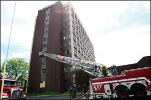 Fire crews stand by at the closed Clarion hotel on Reynolds Road in South Toledo after a fire broke out on June 1.