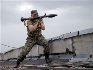 A pro-Russian rebel prepares to fire a rocket propelled grenade during clashes as they attack a border guard base held by Ukrainian troops on the outskirts of Luhansk, eastern Ukraine, today.