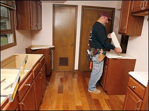 Kevin Krueger installs a countertop during a kitchen remodel in Naperville, Ill. RealtyTrac Inc. said the gross return on investment on flipped houses was 2.3 percent in the last year in Lucas County.