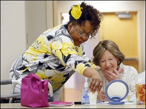Volunteer cosmetologist Brenda Holsey, left, helps Liza Lacy of Toledo with her new makeup during a 'Look Good, Feel Better' event at Mercy St. Anne Hospital on Monday.